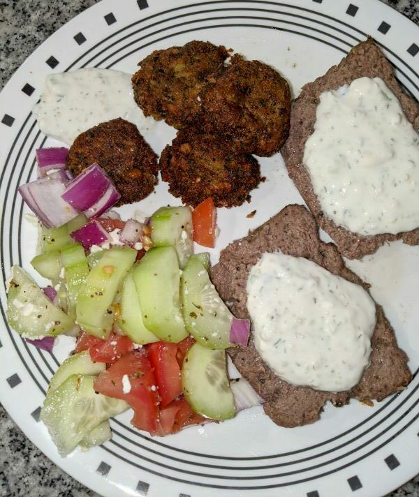 Plate containing Greek Cucumber Salad, Falafel, Tzatiki Sauce, and Lamb and Ground Beef Gyros