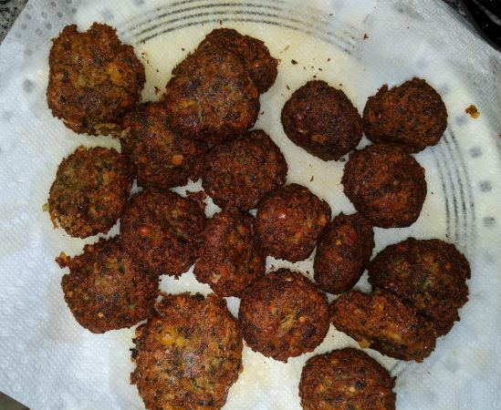 Falafel on a paper towel lined plate after frying