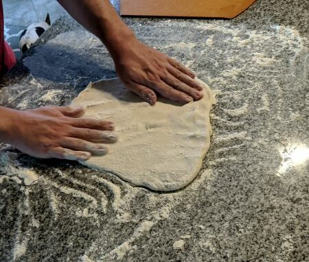 Man Stretching Pizza Dough on floured counter