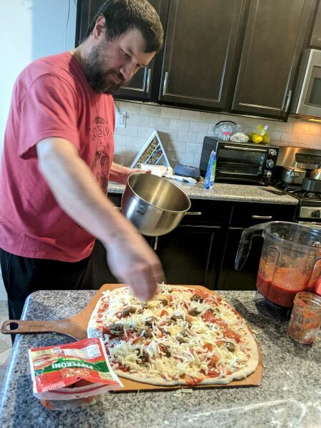 Man putting cheese on pizza
