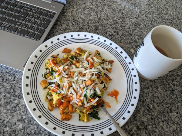 Omelette topped with Cheese, Plated next to coffee and laptop