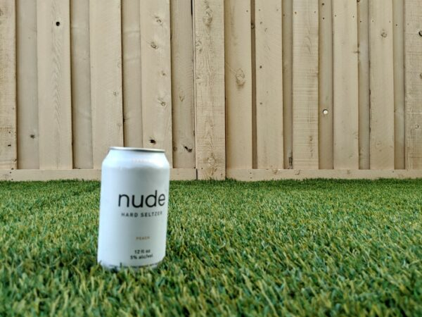 Peach Nude Hard Seltzer can in grass