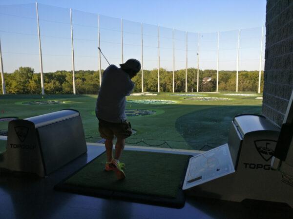 Man golfing at Top Golf Kansas