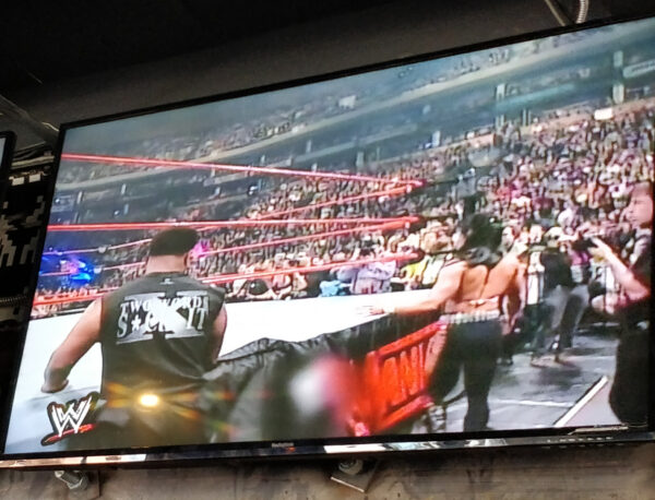 tv screen with wrestling match at at Up Down Kansas City